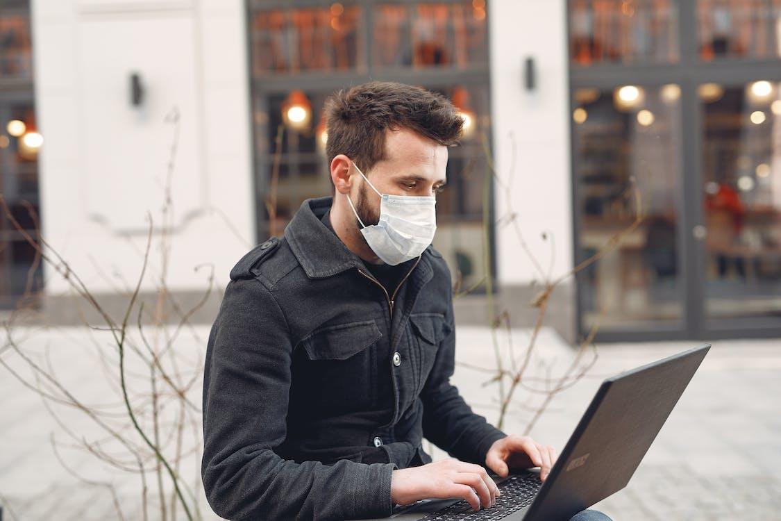 Focused businessman in medical mask using laptop on urban street