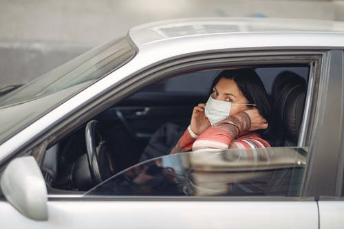 Female driver wearing warm outfit adjusting protective facial mask while sitting in auto with opened window during coronavirus pandemic in city and looking at camera