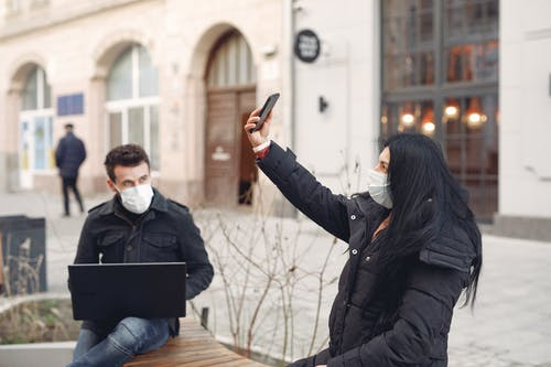 Young couple wearing medical masks using laptop and smartphone on city street