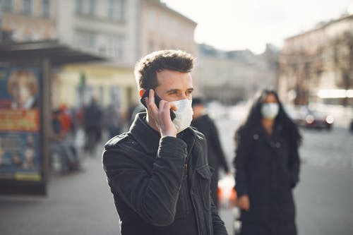 Young man in medical mask speaking on smartphone on urban street during coronavirus pandemic