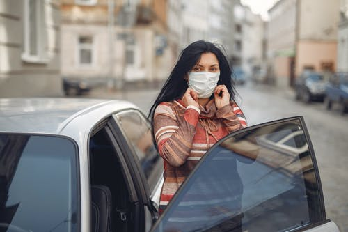 Young woman wearing medical mask standing near automobile on empty urban street