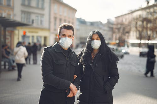 Man in Black Jacket and Woman in Black Coat Wearing White Mask