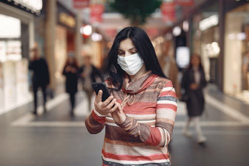 Young woman wearing medical mask taking selfie in shopping center