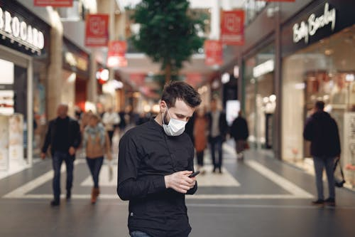 Young man in disposable mask using smartphone in middle of shopping center