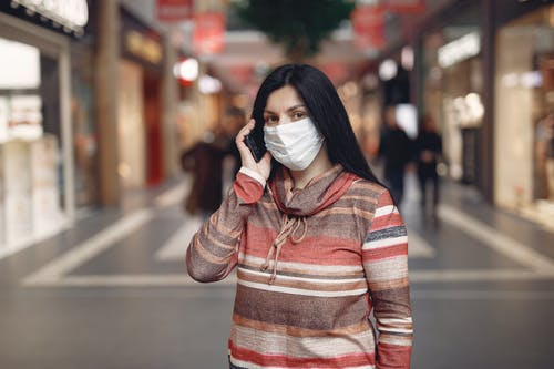 Serious ethnic female in mask talking on mobile phone in modern building