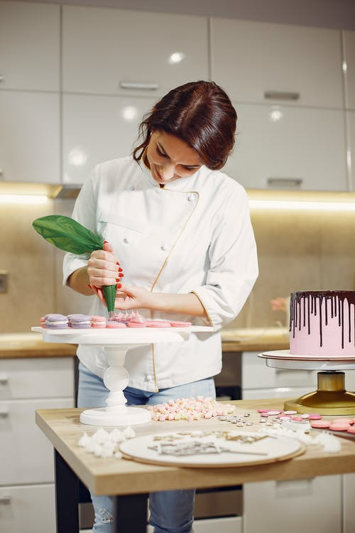 Young woman preparing delicious desserts in bakery