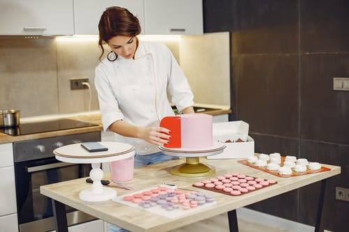 Focused female pastry chef preparing cake and desserts with smartphone aside in modern kitchen