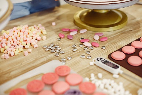 Pink and White Heart Shaped Candies on Brown Wooden Table