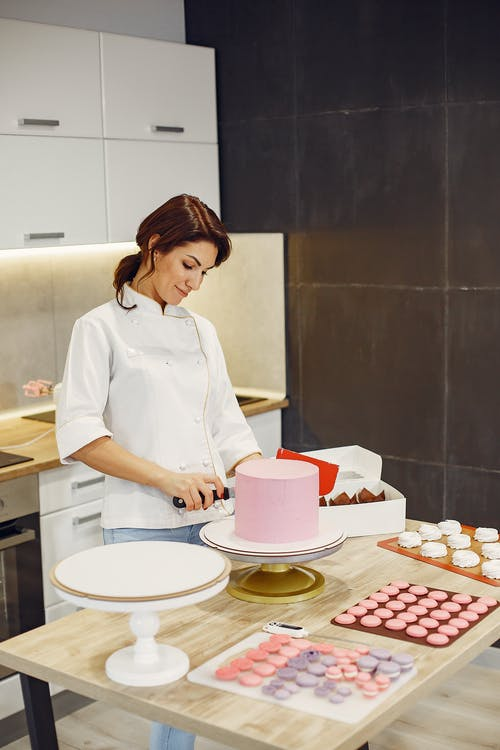 Happy woman in process of cooking fresh cake and pastries in modern laboratory