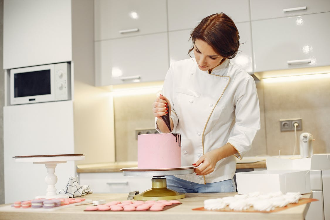 Concentrated female pastry cook decorating cake with pleasure in modern restaurant