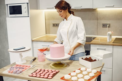 Serious young woman in apron preparing desserts in modern confectionery