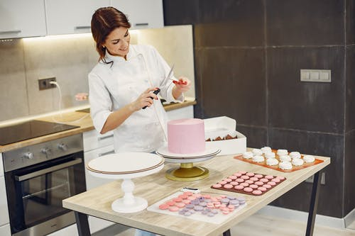 Happy woman preparing kitchen tools during process of making delicious desserts in confectionery