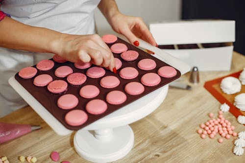 Faceless female pastry cook preparing yummy macaroons in light kitchen