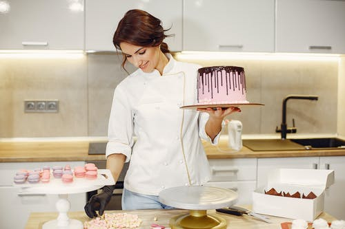Woman in White Button Up Shirt Holding Pink Plastic Fork