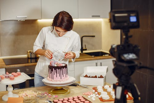 Woman in White Shirt Decorating Cake