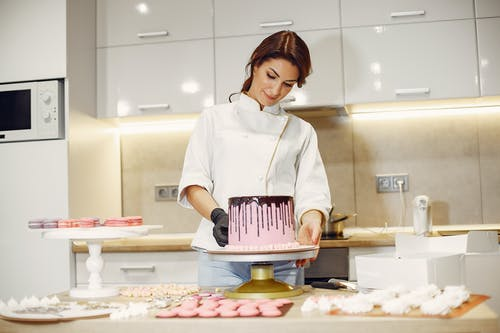 Woman in White Button Up Shirt Holding Pink and White Plastic Tray