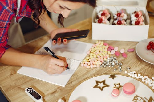 Woman taking notes in notebook among pastry decorations