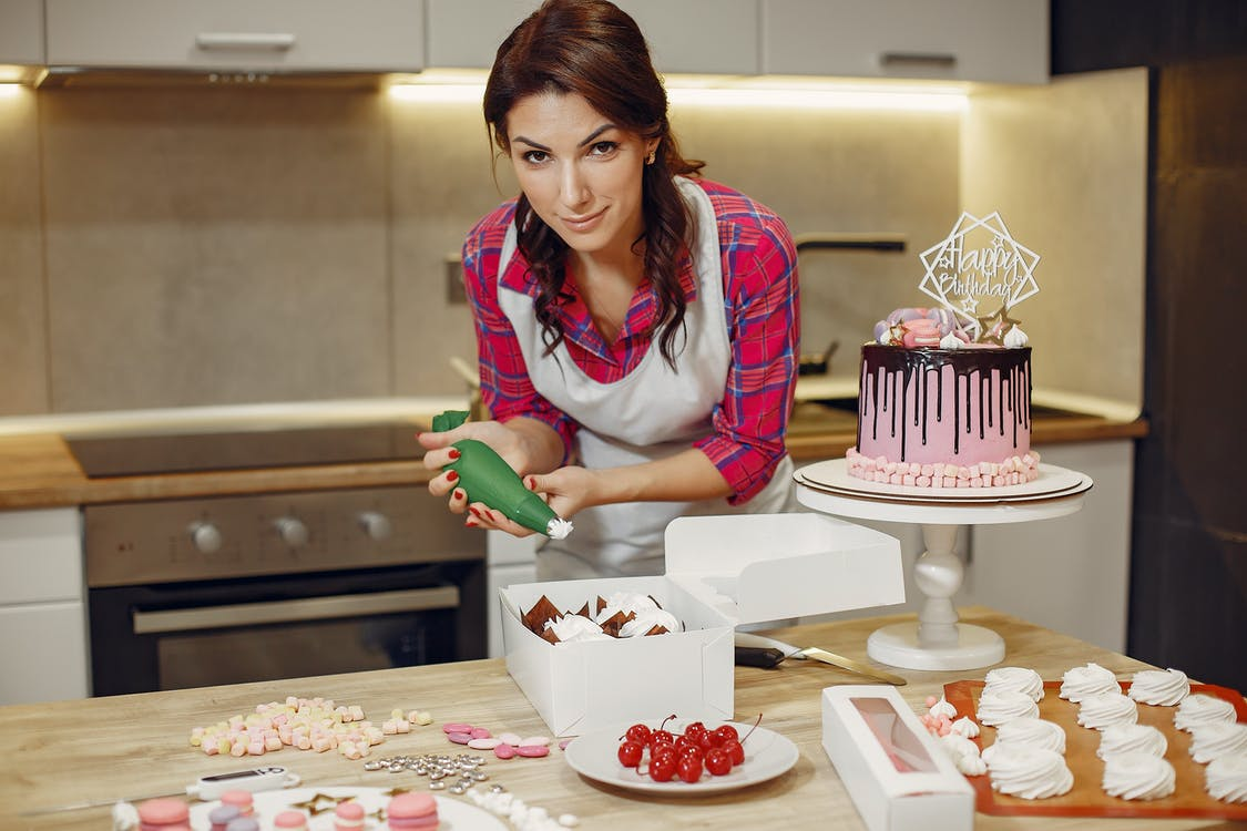 Woman in Red Checked Shirt Icing a Cake