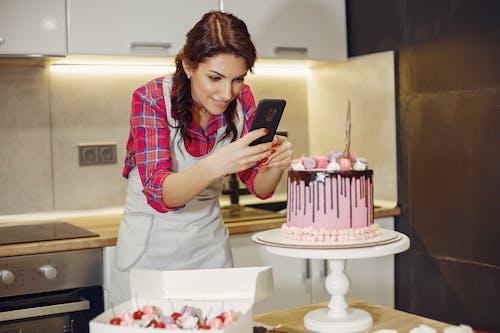 Glad woman taking photo of cake on kitchen