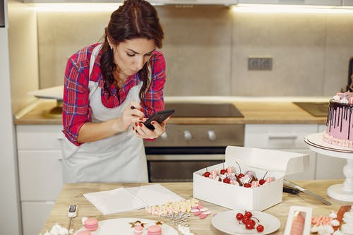Woman in Red Checkered Plaid Button Up Shirt and White Apron Holding Black Smartphone