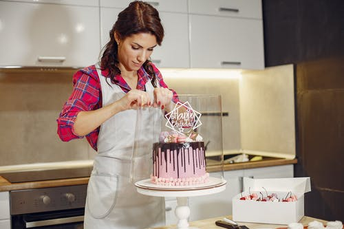 Concentrated woman packing holiday cake