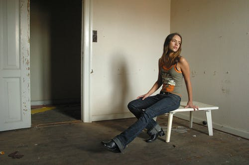 Slim dreamy woman sitting on table in old apartment