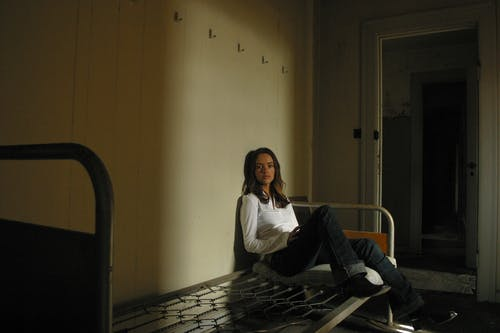 Woman in White Long Sleeve Shirt and Black Pants Sitting on a Bed