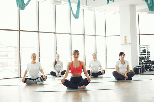 Group of Women Sitting on Blue Yoga Mats