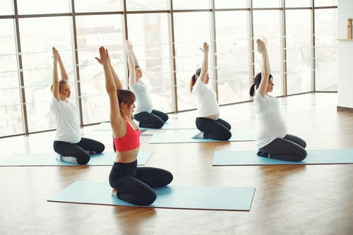 Woman in White Tank Top and Black Leggings Doing Yoga