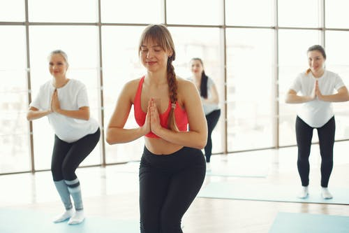 Group of pregnant women in activewear doing yoga meditating with instructor in modern studio of fitness center