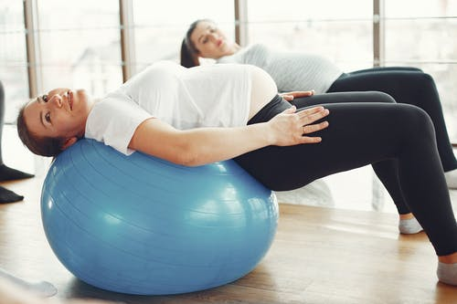 Woman in White T-shirt and Black Leggings Stretching on Blue Exercise Ball