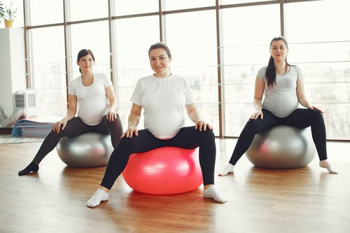 3 Women in White Long Sleeve Shirt and Black Leggings Sitting on Red Exercise Ball