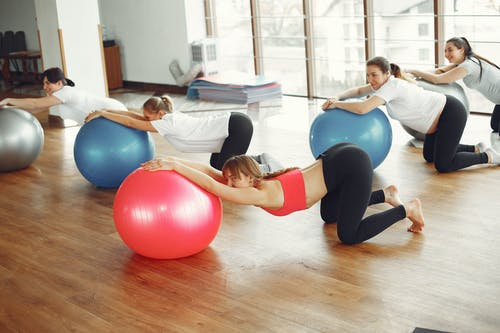 Pregnancy group practicing with fit ball in fitness class
