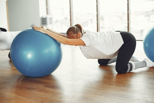 Young pregnant woman doing stretching exercise with fit ball