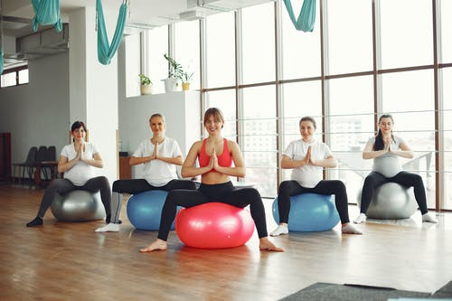 Cheerful group of pregnant women practicing yoga in modern studio