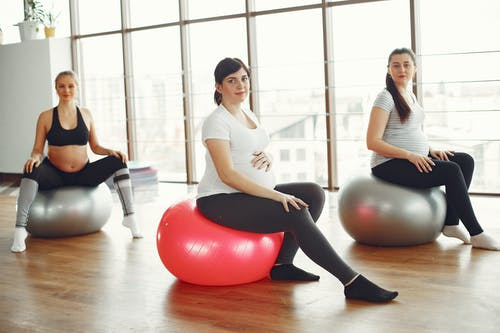 Content young pregnant women during fitness workout in modern studio