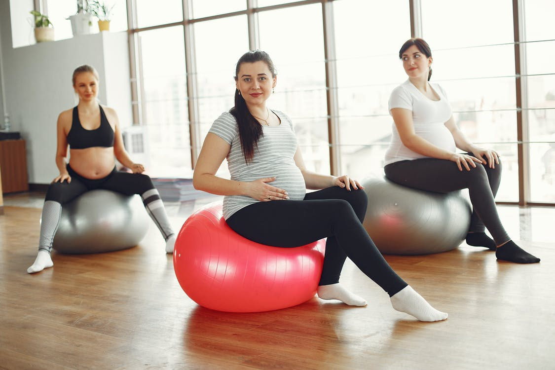 Calm pregnant ladies sitting on fit balls during prenatal training in spacious light gym class at daytime while caring about health