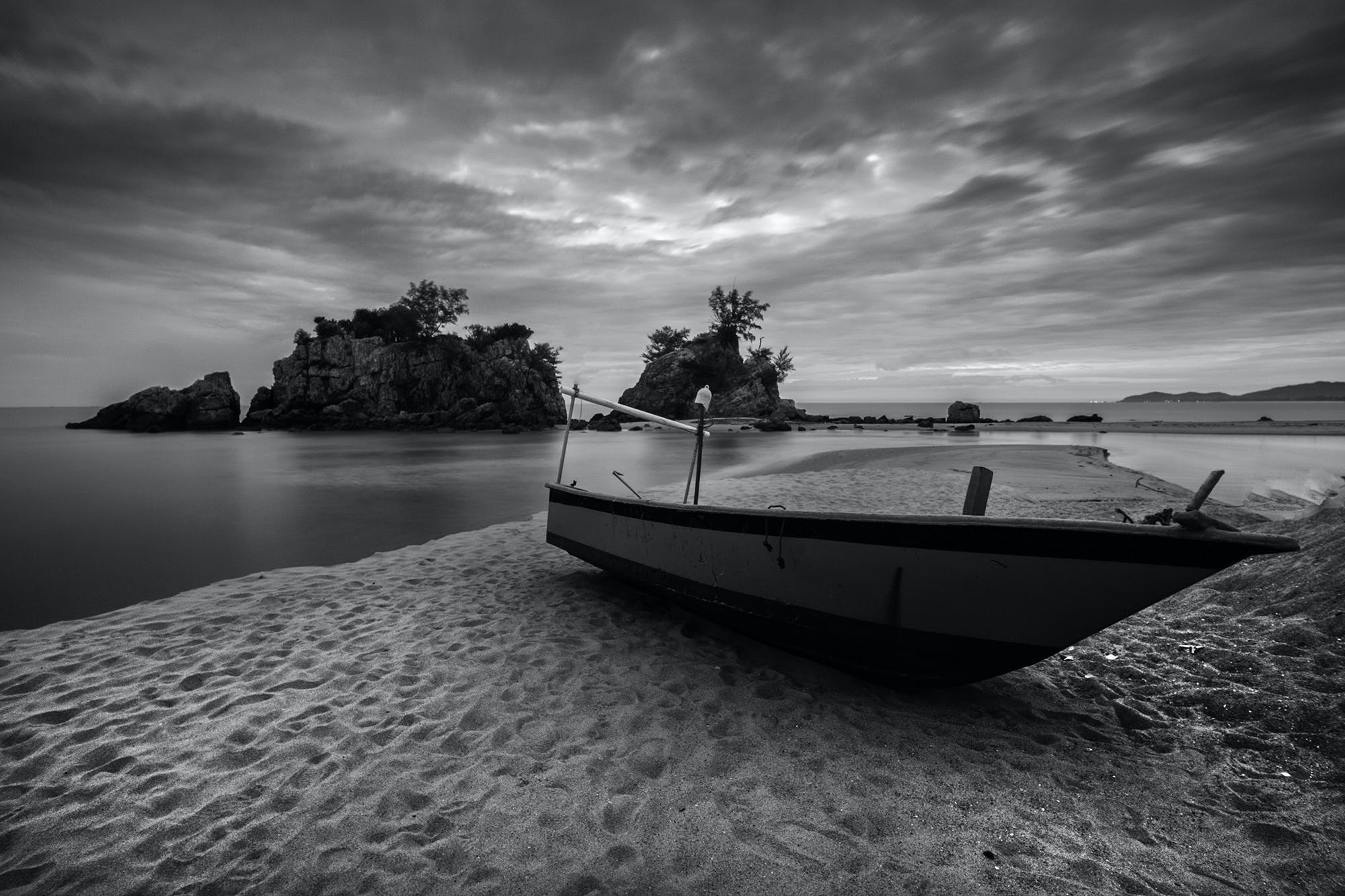 Gray Scale Photography of Brown Boat on Seashore