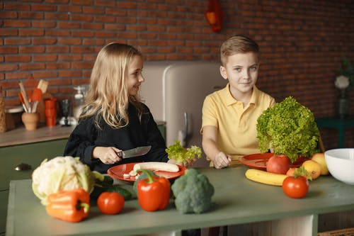 Adorable children with fresh vegetables and fruits cooking