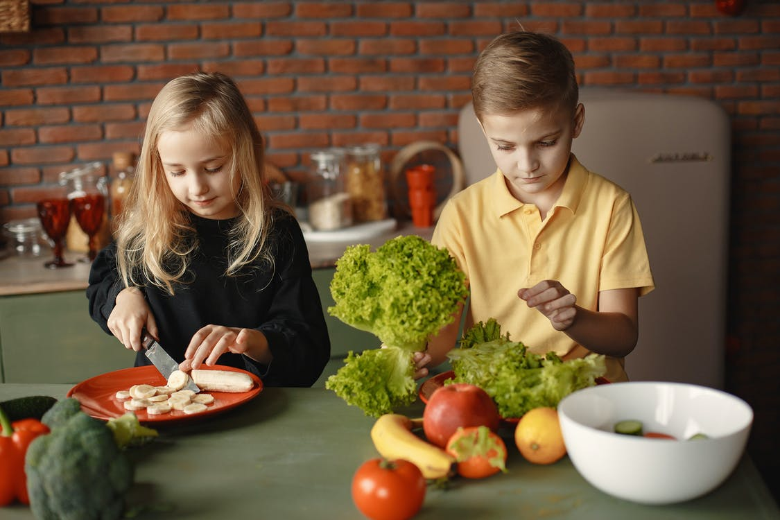 Adorable children cutting with knife while preparing healthy food together