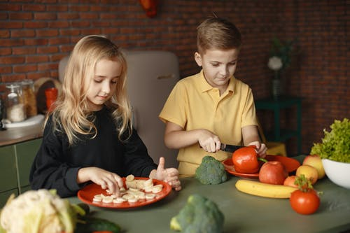 Cute children preparing healthy vegan food together