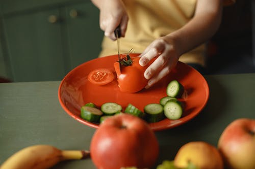 Person Holding Red Tomato on Green Round Plate
