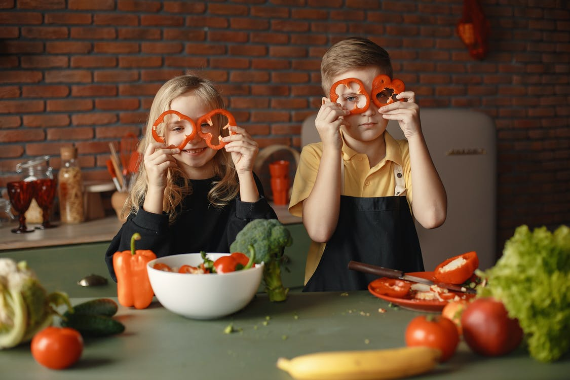 Playful little children with assorted vegetables and fruits in loft kitchen