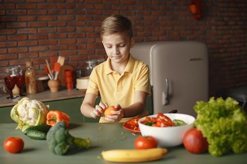 Focused little boy cooking healthy food