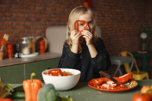 Playful little girl with various vegetables and fruits in loft kitchen