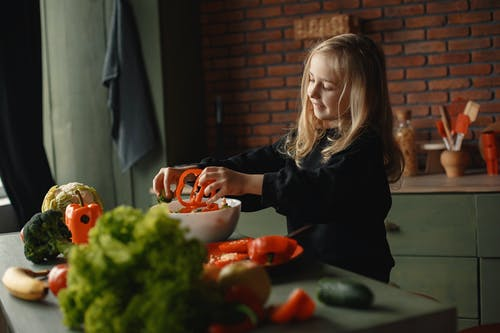 Happy little girl preparing healthy salad in kitchen with loft interior