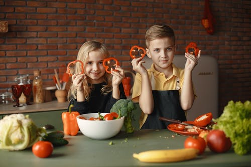 Children in the Kitchen Holding Slices of Capsicum
