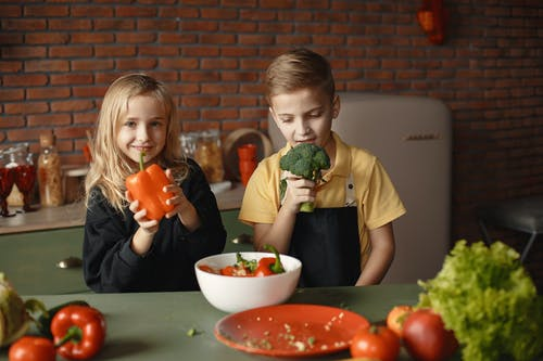 Adorable children during healthy food preparation in loft kitchen
