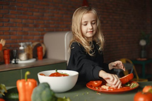 Content little girl preparing vegetable salad in kitchen at home