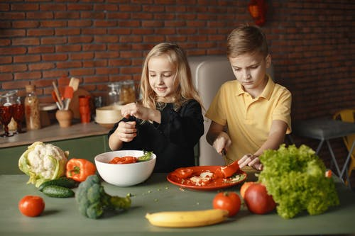 Children preparing vegetable salad in kitchen at home